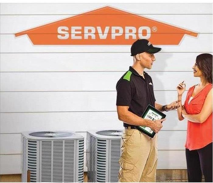Picture of a Servpro Franchise Professional talking to Female Customer in front of an residential HVAC Unit